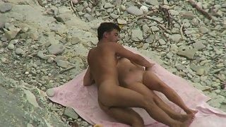 Secret voyeur cam recording suntanned paramours penetrating on a pebble shore