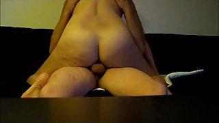 Pauline sitting astride her lover on the sofa enjoying him in her vulva