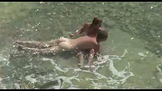 Voyeur sex duo filmed having hook-up in the river on a pebble beach